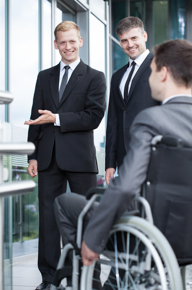 Businessman showing welcome gesture to disabled worker, vertical